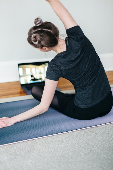 picture of lady exercising in front of a laptop screen